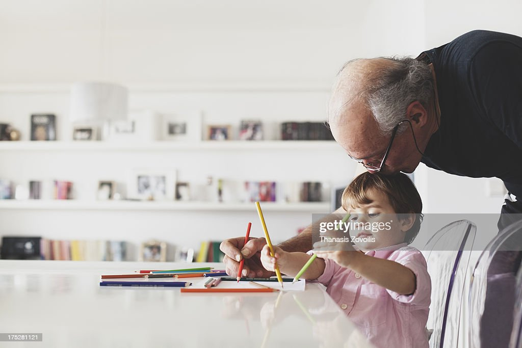 Grandfather help his grandson with drawing : Stock Photo