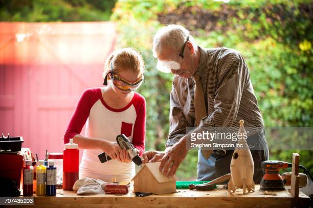 grandfather helping granddaughter build birdhouse in garage - birdhouse stock pictures, royalty-free photos & images