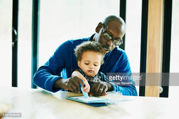 Grandfather helping granddaughter color at dining room table