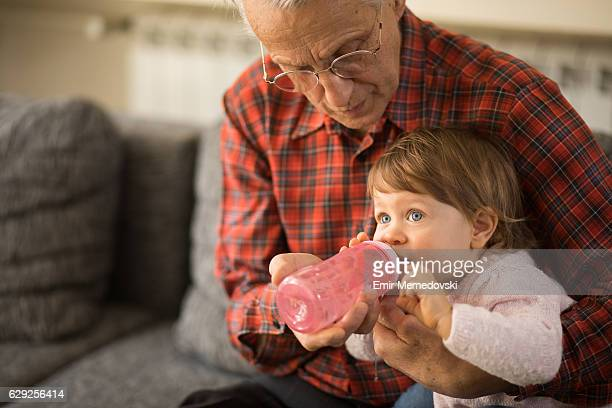 Grandfather helping granddaughter drink water from baby bottle