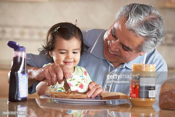 Grandfather helping granddaughter (12-15 months) make sandwich