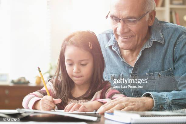 Grandfather helping granddaughter with homework