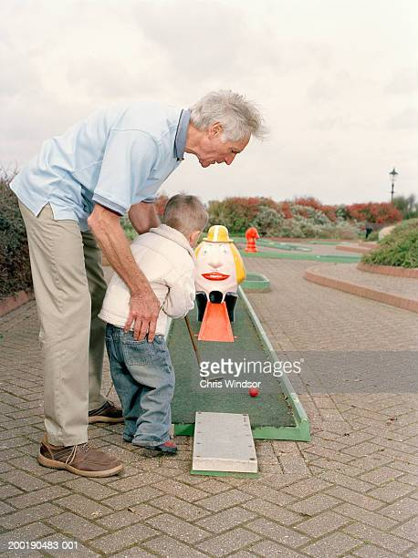 grandfather helping grandson (3-5) play crazy golf - miniature golf stock photos and pictures