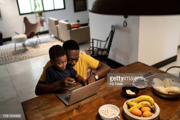 grandfather helping grandson studying or working at home - mindzoom 2 stock pictures, royalty-free photos & images