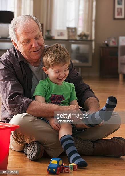 Grandfather helping grandson to put on socks