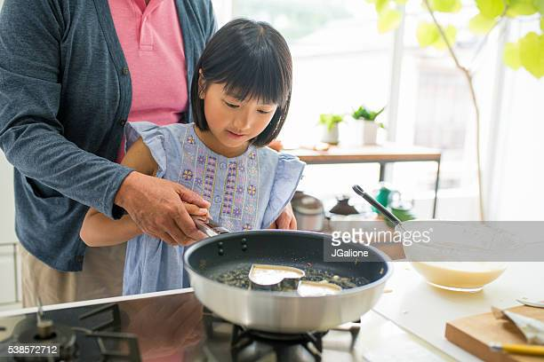 Grandfather helping his grandaughter to cook