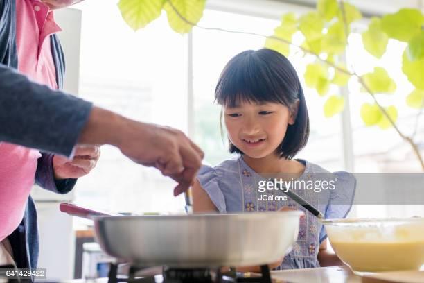 祖父が grandaughter 料理をお手伝いします。