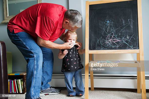 grandfather helping his granddaughter (12-23 months) to blow nose - 12 23 months stock pictures, royalty-free photos & images