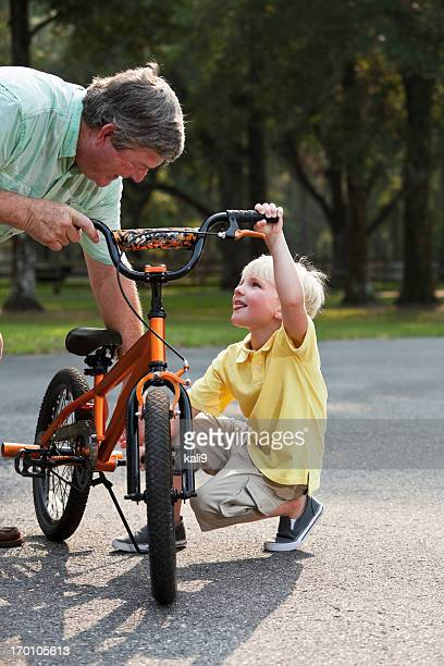 Grandfather helping little boy with bicycle