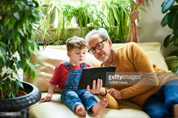 grandfather helping young grandson on digital tablet - real people stock pictures, royalty-free photos & images