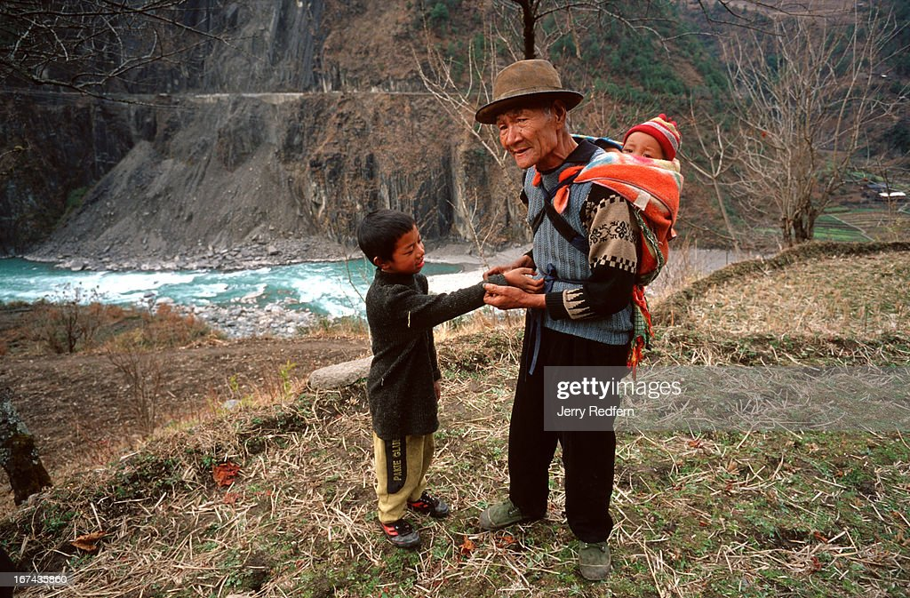 A grandfather helps his grandson roll up his sleeves, in a ricefield above the Nujiang River in rural Yunnan Province. .