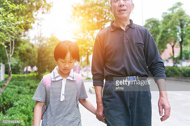 grandfather hold hand with his granddaughter