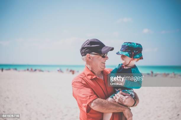 Großvater Holding Baby Boy am tropischen Strand, Kuba