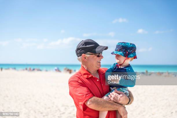grandfather holding baby boy on tropical beach, cuba - sun hat stock pictures, royalty-free photos & images