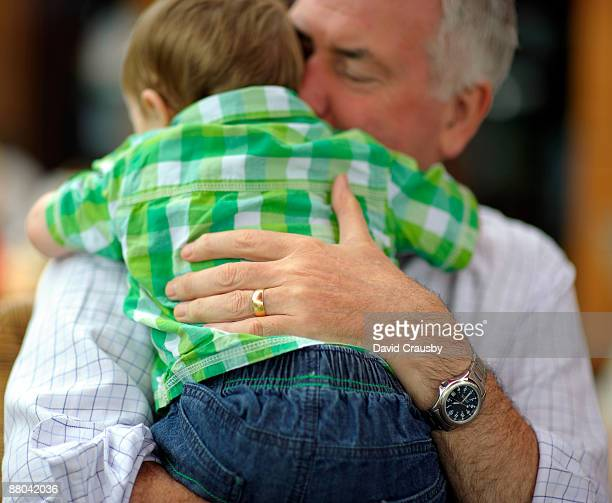 grandfather holding baby grandson - crausby stock pictures, royalty-free photos & images