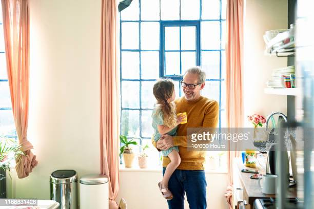 grandfather holding granddaughter and smiling in kitchen - active seniors stock pictures, royalty-free photos & images
