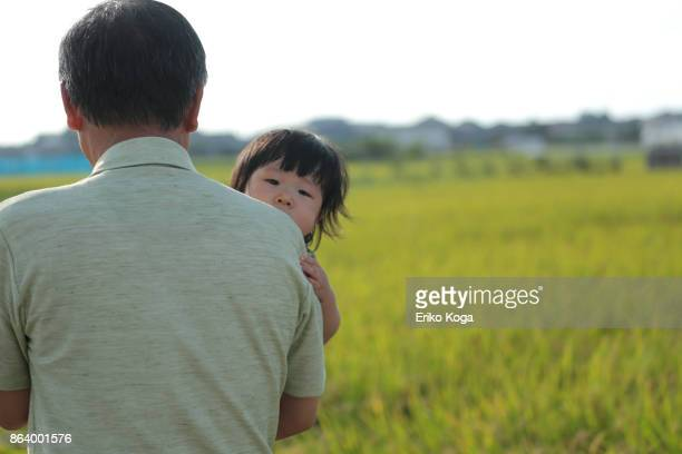 Grandfather holding granddaughter outside