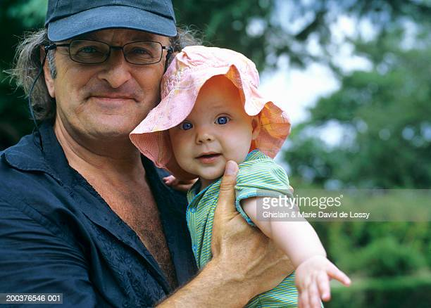grandfather holding granddaughter (9-12 months), smiling, portrait - female hairy chest stock pictures, royalty-free photos & images