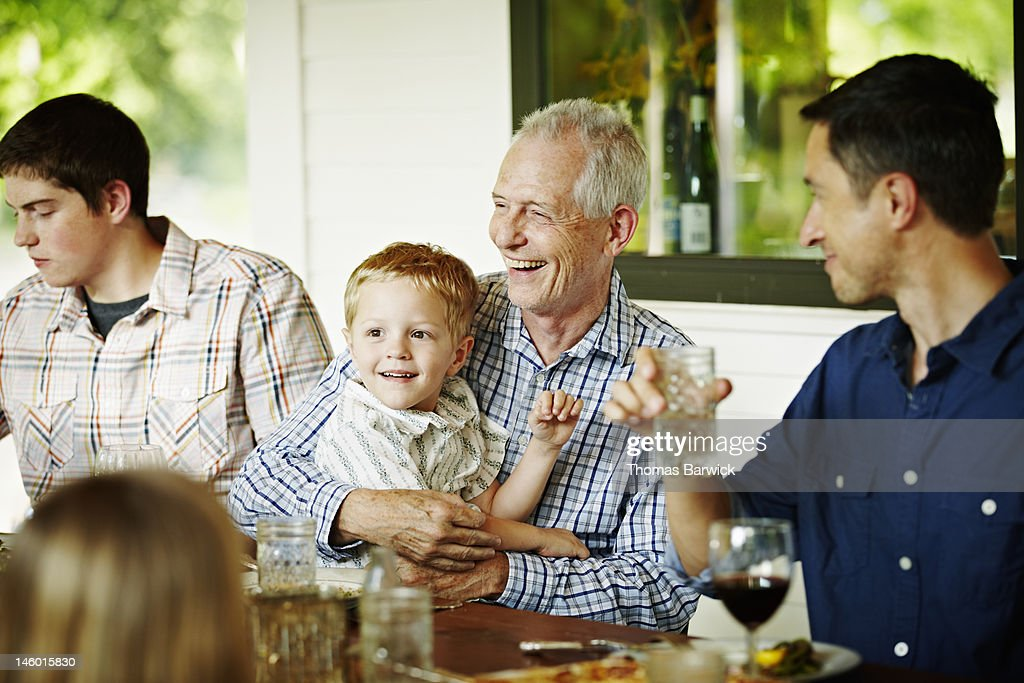 Grandfather holding grandson on lap at table : Stock Photo