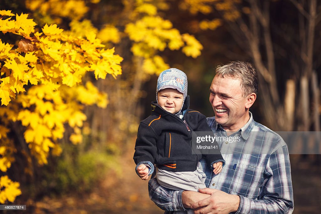 grandfather holding his grandchild on arm, autumn : Stock Photo