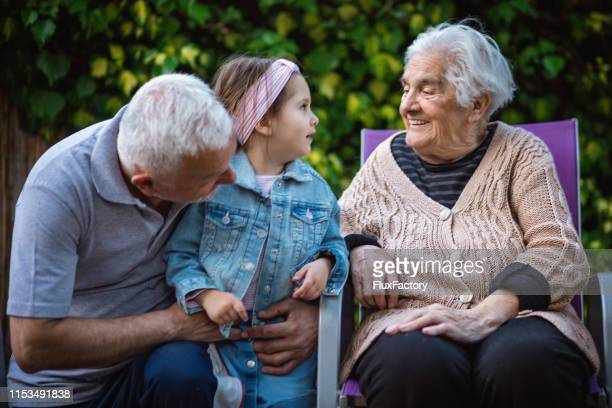 grandfather holding his granddaughter while she talking with great-grandmother - great granddaughter stock photos and pictures