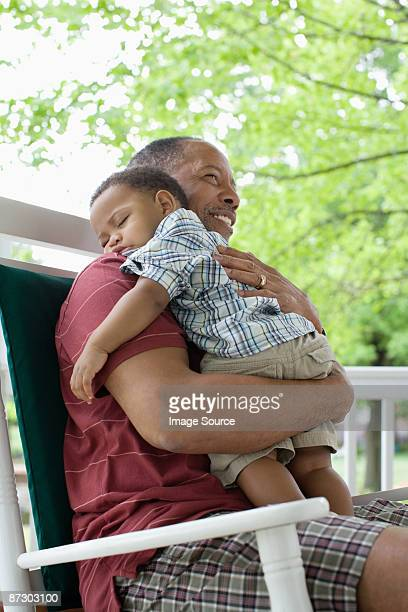 A grandfather holding his sleeping grandson