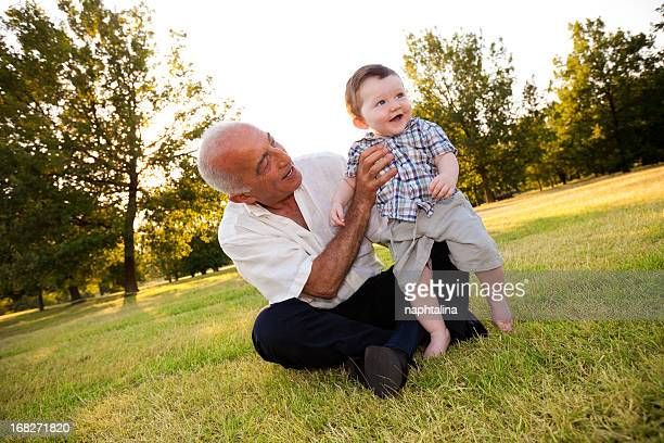 grandfather holding nephew at park - nephew stock pictures, royalty-free photos & images