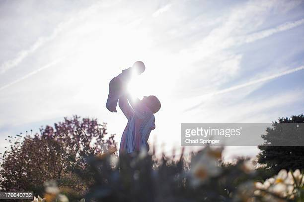 Grandfather holding up baby girl in garden