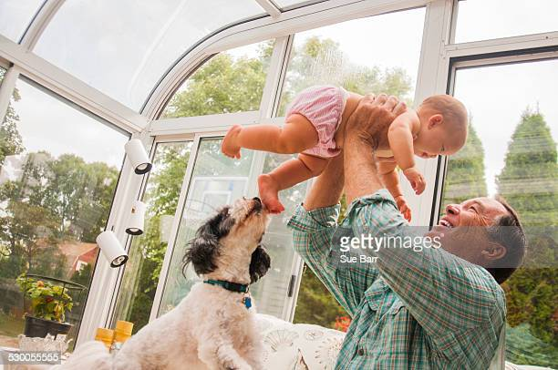Grandfather holding up baby granddaughter in conservatory