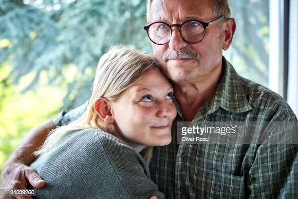 grandfather hugging adult granddaughter at the window - pareja hombre mayor y mujer joven fotografías e imágenes de stock