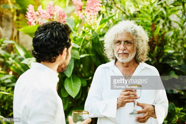 Grandfather in discussion with family members during backyard dinner party