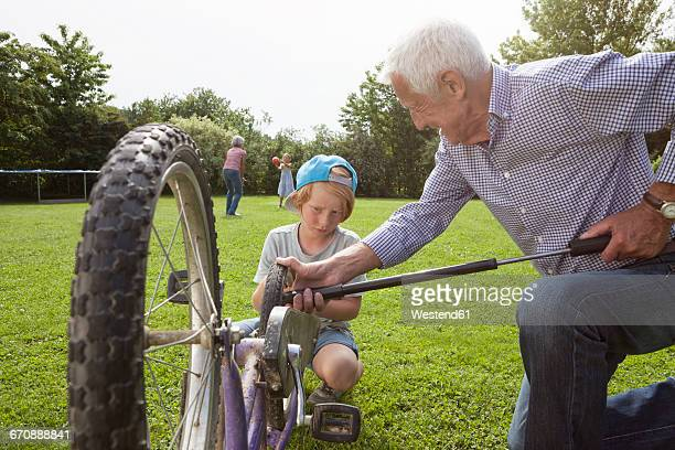 Grandfather inflating grandsons bicycle in garden