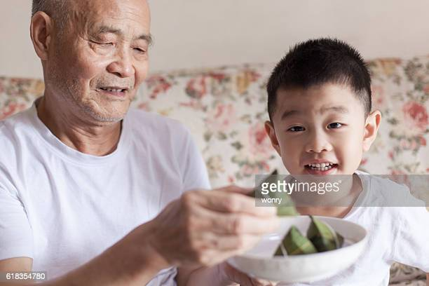 Grandfather introducing grandson to zongzi