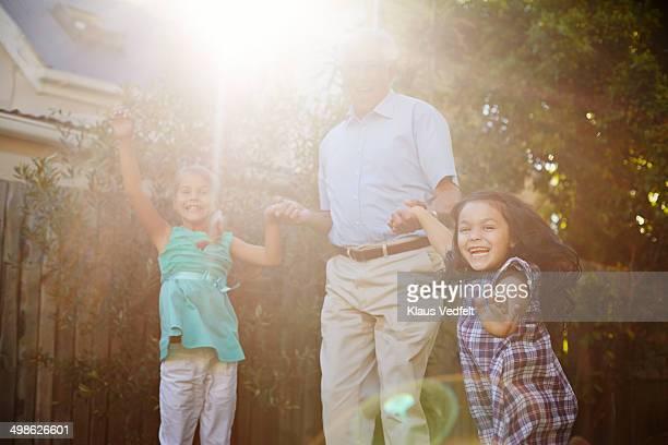 Grandfather jumping with children in garden