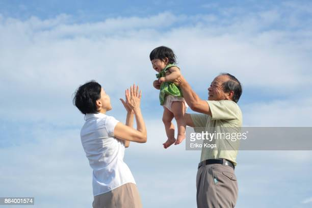 Grandfather lifting up granddaughter and grandmother crapping her in the open air