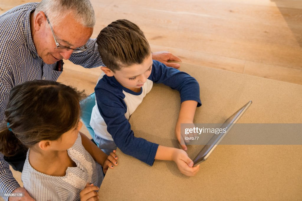 Grandfather, look this game. : Stock Photo