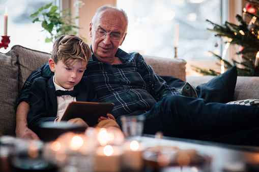 Grandfather looking at digital tablet while sitting with grandson in living room during Christmas - gettyimageskorea