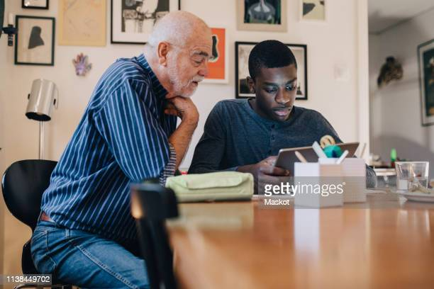 grandfather looking at grandson doing research over digital tablet at table against wall in living room - african american man helping elderly stock pictures, royalty-free photos & images