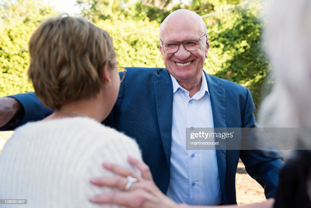Grandfather of millennial bride at wedding cocktail in backyard. : Stock Photo