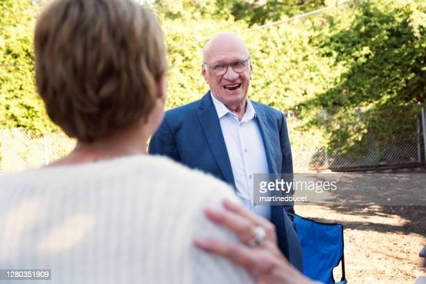 """grandfather of millennial bride at wedding cocktail in backyard. - """"martine doucet"""" or martinedoucet stock pictures, royalty-free photos & images"""