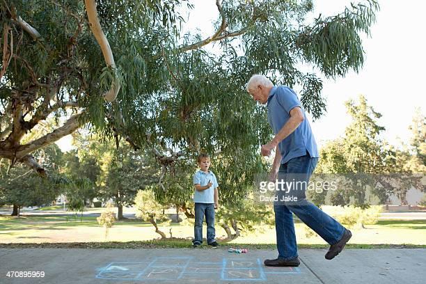 Grandfather on hopscotch, boy watching