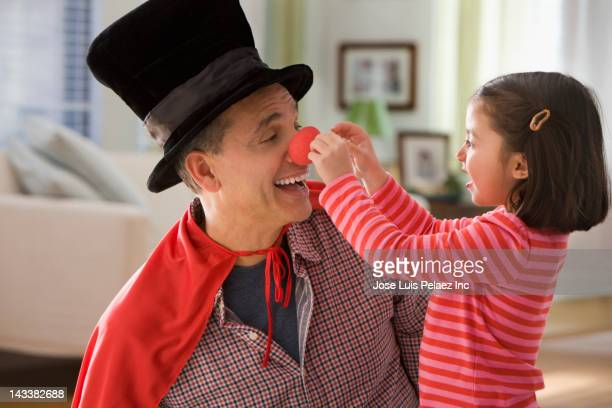 grandfather performing magic for granddaughter - clown's nose stock photos and pictures