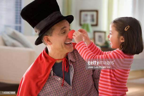 grandfather performing magic for granddaughter - nariz de payaso fotografías e imágenes de stock