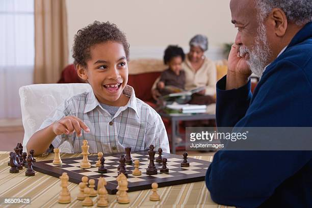 grandfather playing chess with grandson - playing chess stock pictures, royalty-free photos & images