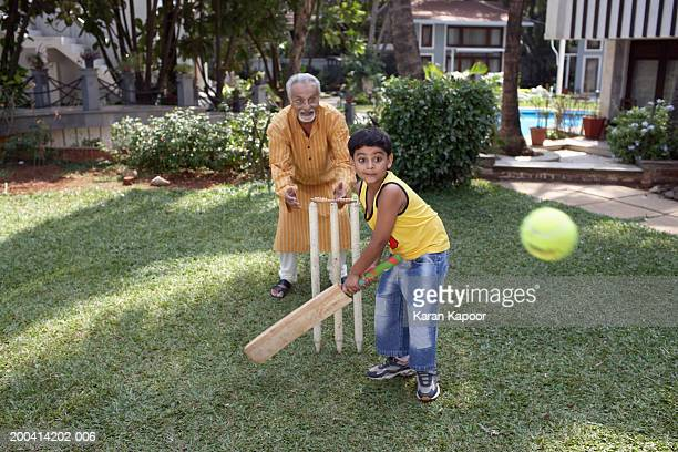 grandfather playing cricket with grandson (6-8) batting ball - batting sports activity stock photos and pictures