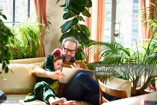 grandfather playing game on laptop with granddaughter - dinosaur stock pictures, royalty-free photos & images