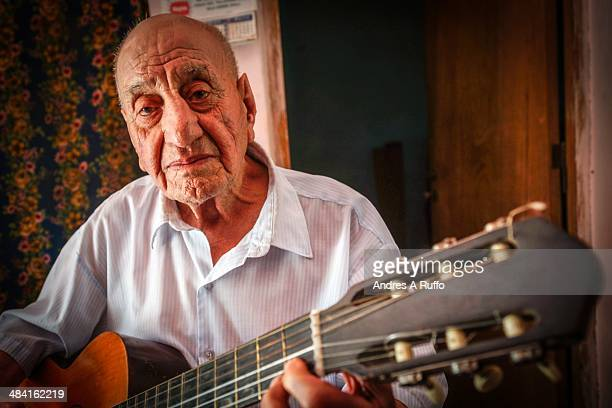 Grandfather playing guitar close family a character well known in Isla Verde Cordoba Argentina