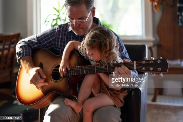 grandfather playing guitar with granddaughter at home - midsection stock pictures, royalty-free photos & images