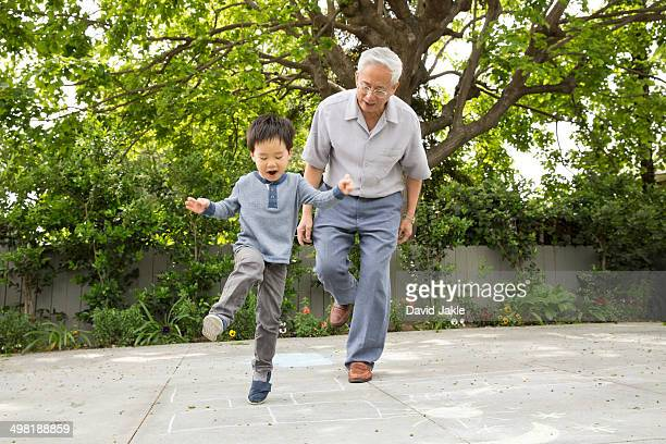 Grandfather playing hopscotch with grandson