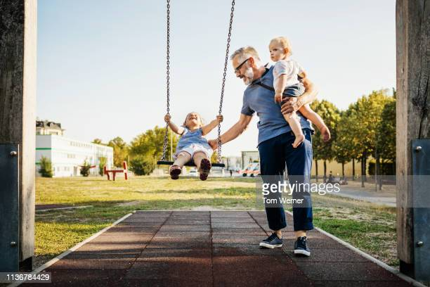 grandfather playing on swing set with grandchildren - swinging stock pictures, royalty-free photos & images